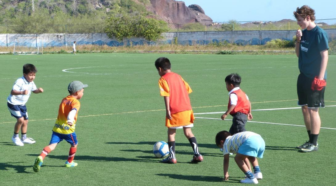 A sports instructor volunteers as a sports coach in Ecuador and leads a football practice